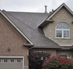 image of a suburban house with large windows and a double car garage, new shingled roof installed by Baron Roofing & Siding