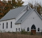 image of a small white church with a new shingled roof, installed by Baron Roofing & Siding