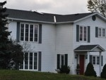 image of a large white house with a Canadian flag out front and a large tree to the left, roof installed by Baron Roofing & Siding