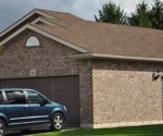 image of a brick suburban home with a blue minivan in the driveway, new roof shingles installed by Baron Roofing & Siding